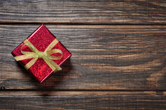 Red gif box. With golden ribbon on wooden background Royalty Free Stock Images