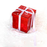 Red gift. In a snowy background Royalty Free Stock Photo