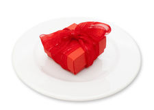Red gift. For a christmast evening on white plate Stock Image
