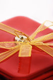 Red gift. Closeup of a yellow ribbon on a red gift box, isolated on white background royalty free stock photography