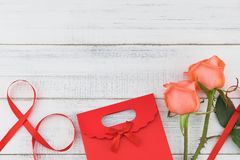 Red gift bag decorated with orange roses and red ribbon Royalty Free Stock Images