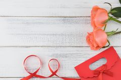 Red gift bag decorated with orange roses and red ribbon Stock Photo