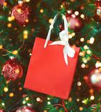 Red gift bag with a white bow hanging on the Christmas tree stock photo