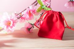 Red Gift Bag and plum blossom on Old Shabby Wooden Table concept Christmas and Newyear. Red Gift Bag and plum blossom on Old Shabby Wooden Table concept Royalty Free Stock Image