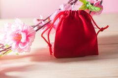 Red Gift Bag and plum blossom on Old Shabby Wooden Table concept Christmas and Newyear. Red Gift Bag and plum blossom on Old Shabby Wooden Table concept royalty free stock images