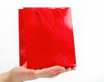 Red gift bag in the women's hands on a white. Red gift bag in the women's hands on a white background Stock Image