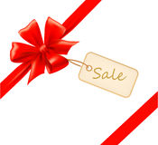 Red gift bow with ribbons and sale label. Stock Photos