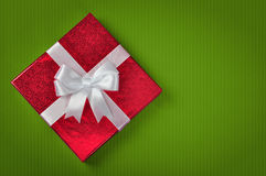 Red gift box. With white ribbon on green background Stock Image