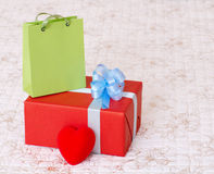 Red gift box. With a heart and a green bag Royalty Free Stock Images