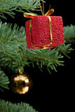 Red gift box and bauble on pine branch Royalty Free Stock Image