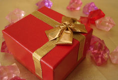 Red gift box on a beautiful golden background stock photos