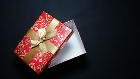 Red gift box on black background.  Royalty Free Stock Images