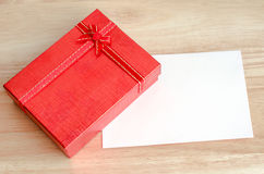 Red gift box and blank white card on wooden table Royalty Free Stock Photo