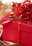 Red gift box with bows and stars. On golden silk background Royalty Free Stock Photography