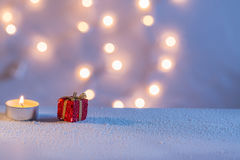 Red gift box and candle. Candle light and red gift box on snow with pastel colors Royalty Free Stock Images