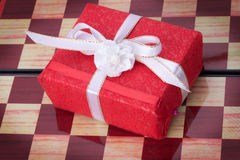 Red gift box on a chessboard Royalty Free Stock Photos