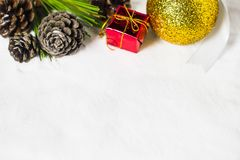 Red gift box, Christmas ball, dry pine cones and green leafs Stock Photography