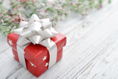 Red gift box with christmas ribbon. On a wooden background Royalty Free Stock Photos