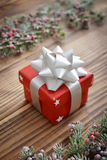 Red gift box with christmas ribbon. On a wooden background Stock Images
