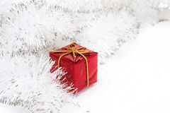 Red gift box and Christmas tinsel on a white background Stock Photography