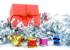 Red gift box with colorful mini drums on white background Stock Images