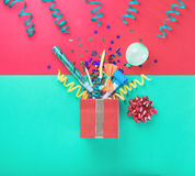 Red gift box with colorful party items Stock Photos