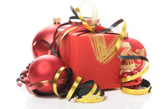 Red gift box with colorful ribbons and xmas baubles Stock Photography
