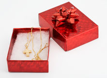 Red gift box with cross on chain within Stock Images