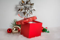 Red gift box and decorations. Red Christmas gift box surrounded by snow and decorations Royalty Free Stock Photos