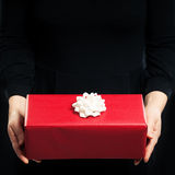 Red Gift Box and Female Hands on Background Royalty Free Stock Images
