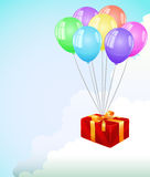Red gift box fly in the clouds at color balloon Stock Images