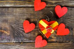 Red gift box in the form it has shaped pendant wooden slipper with diamond, she stands on a wooden background surrounded by decor. Ative hearts. Copy paste stock image