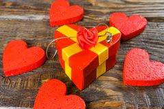 Red gift box in the form it has shaped pendant wooden slipper with diamond, she stands on a wooden background surrounded by decora. Tive hearts. Copy space Royalty Free Stock Photography