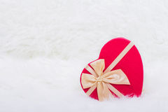 Red gift box in form of heart with beige bow on white furry back. Ground Stock Photo
