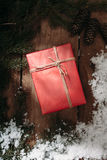 Red gift box and fur tree on wooden background Royalty Free Stock Image