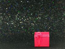 Red gift box on glittery black background Royalty Free Stock Photography
