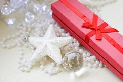 Red gift box, glittery white star and cristmas tree decorations stock photo