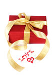 Red gift box with a gold bow Stock Photos