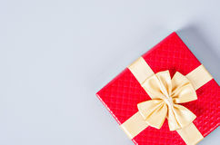 Red gift box with gold ribbon on gray background. Royalty Free Stock Photo