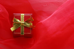 Red gift box with gold ribbon. On scarlet transparent fabric, holiday composition Royalty Free Stock Photos