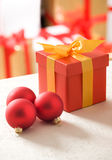 Red gift box with gold ribbon and some glass-balls. Red gift box with gold ribbon and red glass-balls. Bunch of presents in background royalty free stock image