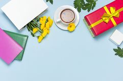 Red gift box with gold ribbon yellow chrysanthemums cup of tea notebook on blue background top view flat lay. Holiday concept, bir. Thday gift, valentine day or stock photo
