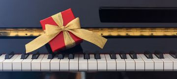 Red gift box on piano keyboard, front view. Red gift box with golden bow on classical piano keyboard, front view Stock Photos