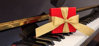 Red gift box on piano keyboard. Red gift box with golden bow on classical piano keyboard Royalty Free Stock Photo