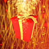 Red gift box with golden ribbon on fantastic background Stock Images
