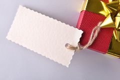 Red gift box with golden ribbon and label close up Stock Photos