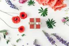 Red gift box golden ribbon white background wildflowers poppy am. Red gift box with golden ribbon on white background with wildflowers, poppy, amaryllis, peonies stock photos