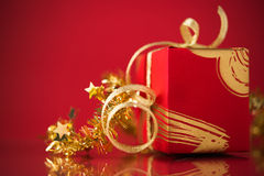 Red gift box with golden ribbons on red background. Stock Photos