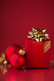 Red gift box with golden ribbons and xmas baubles on red background. Royalty Free Stock Image