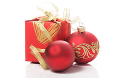 Red gift box with golden ribbons and xmas baubles Stock Photos